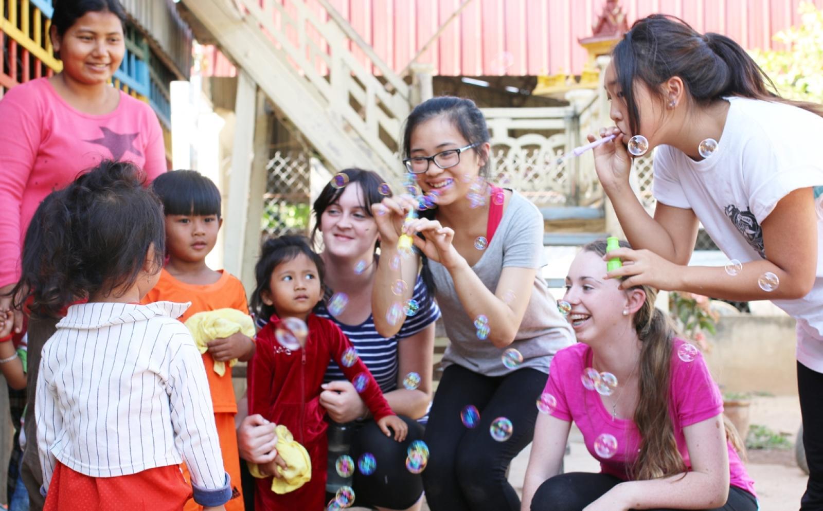 シャボン玉で一緒に遊ぶチャイルドケアボランティアとカンボジアの子供たち